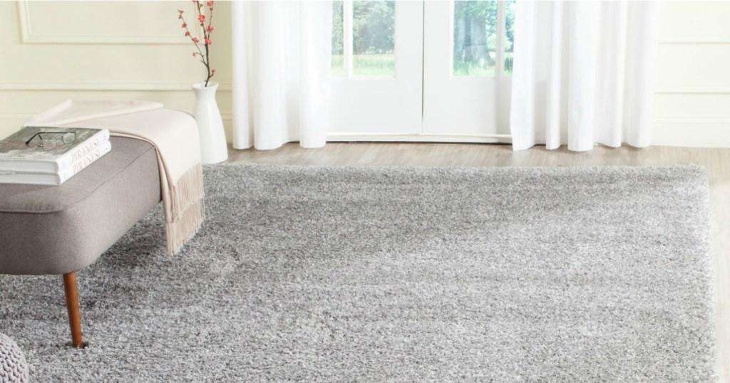 gray rug on wood floor with ottoman on rug