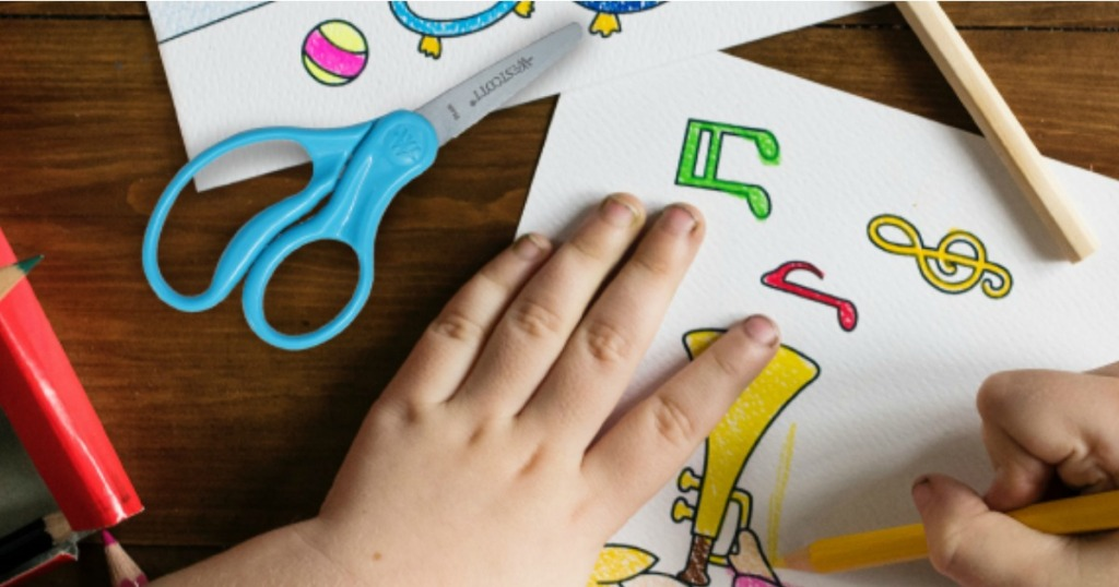 Boy drawing and coloring with pair of scissors next to him