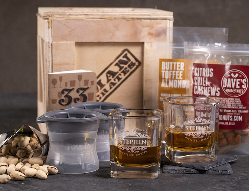 Crate with glasses, whiskey and nuts