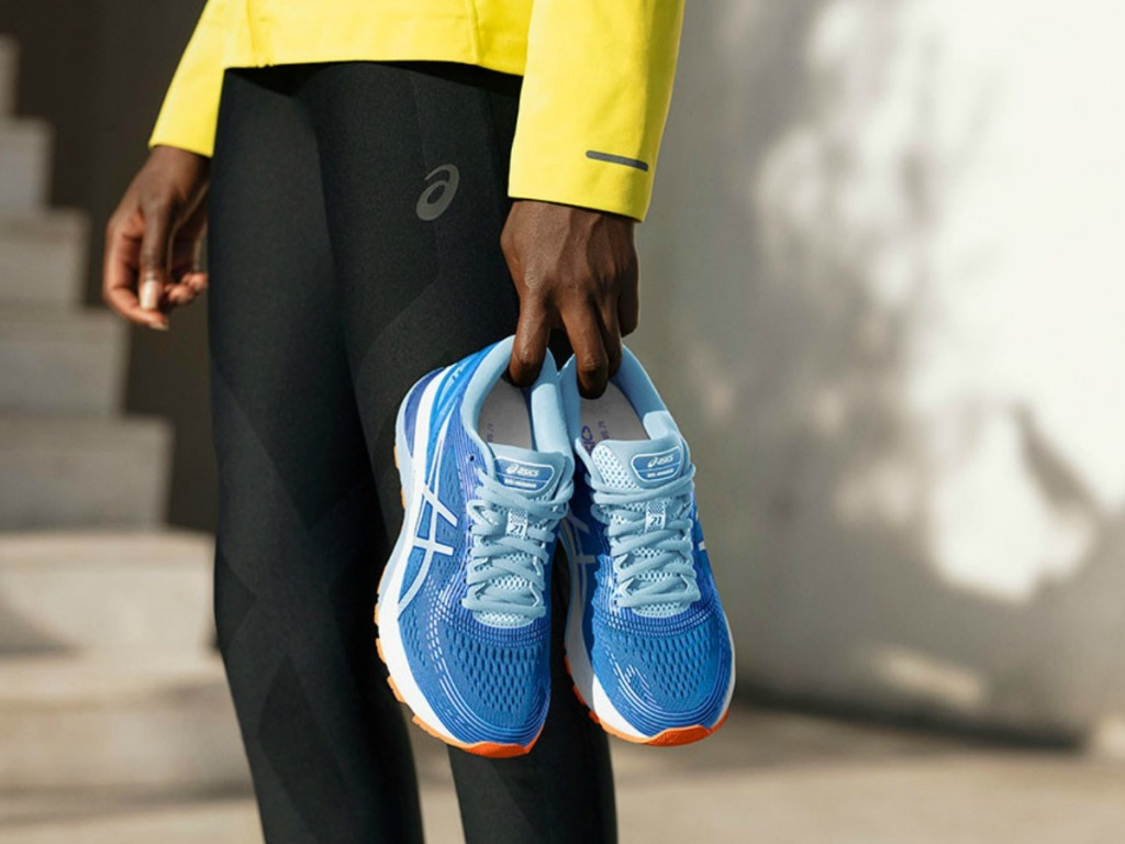 woman holding blue asicsshoes