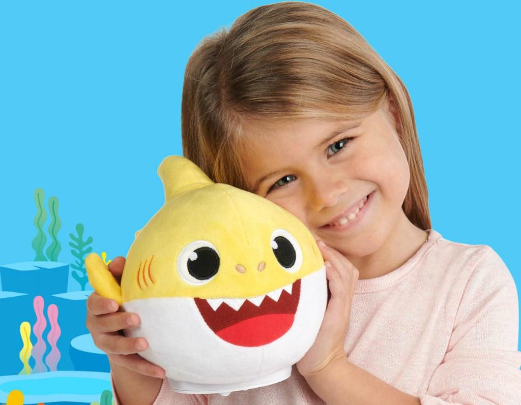 girl holding yellow plush shark toy