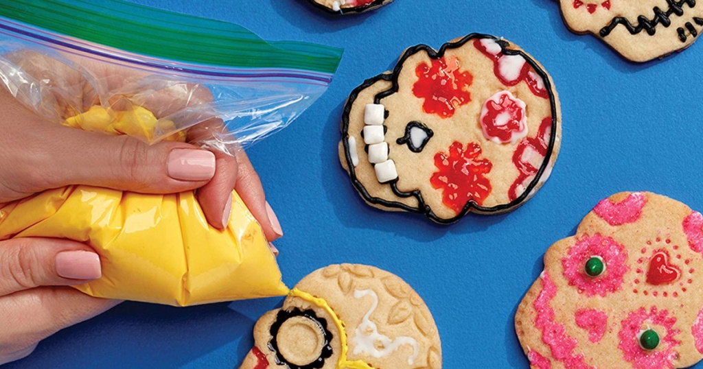 woman squeezing icing out of ziploc bag onto cookies