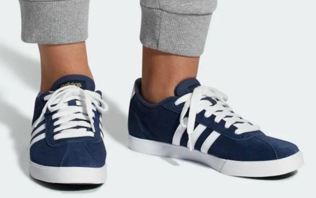 woman wearing dark blue addidas shoes