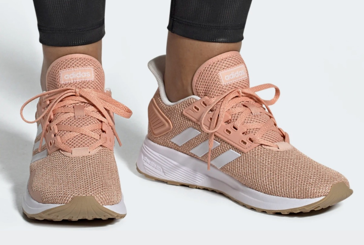 Woman wearing adidas brand women's running shoes in Pink
