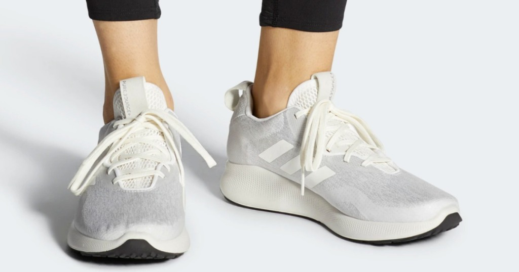 Woman wearing adidas brand shoes in gray and cream colored