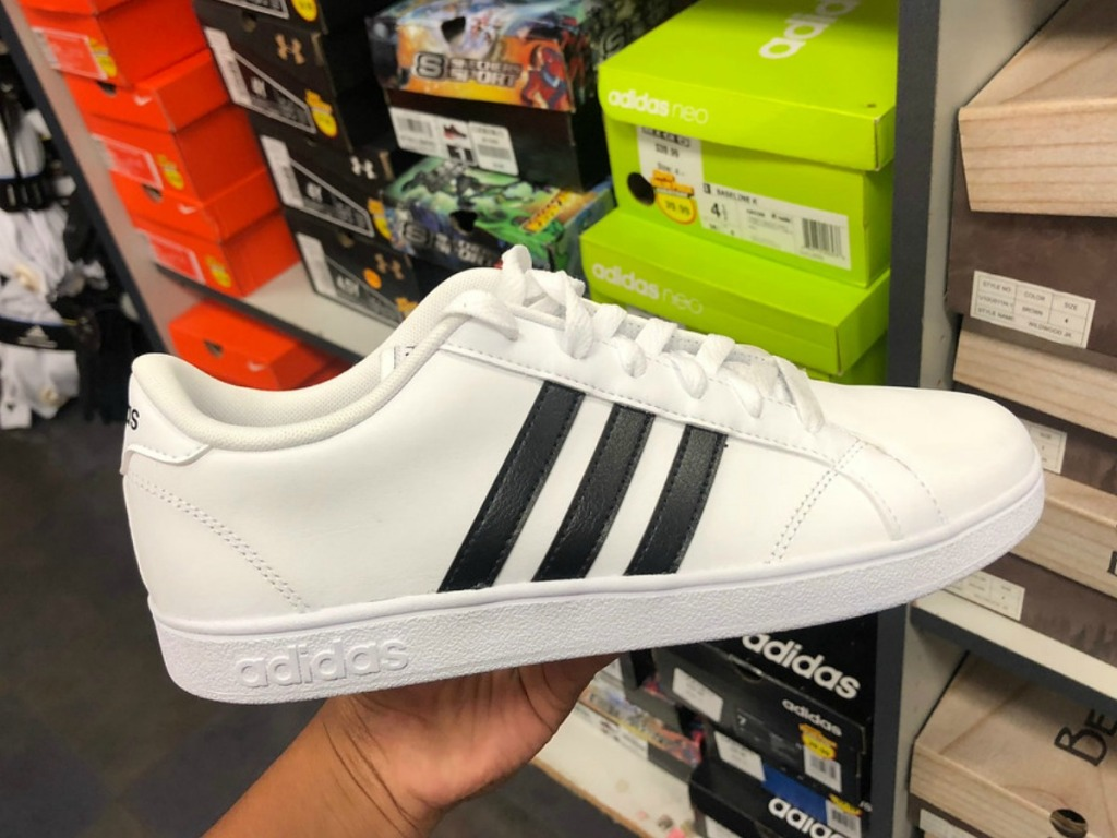 hand holding adidas shoes