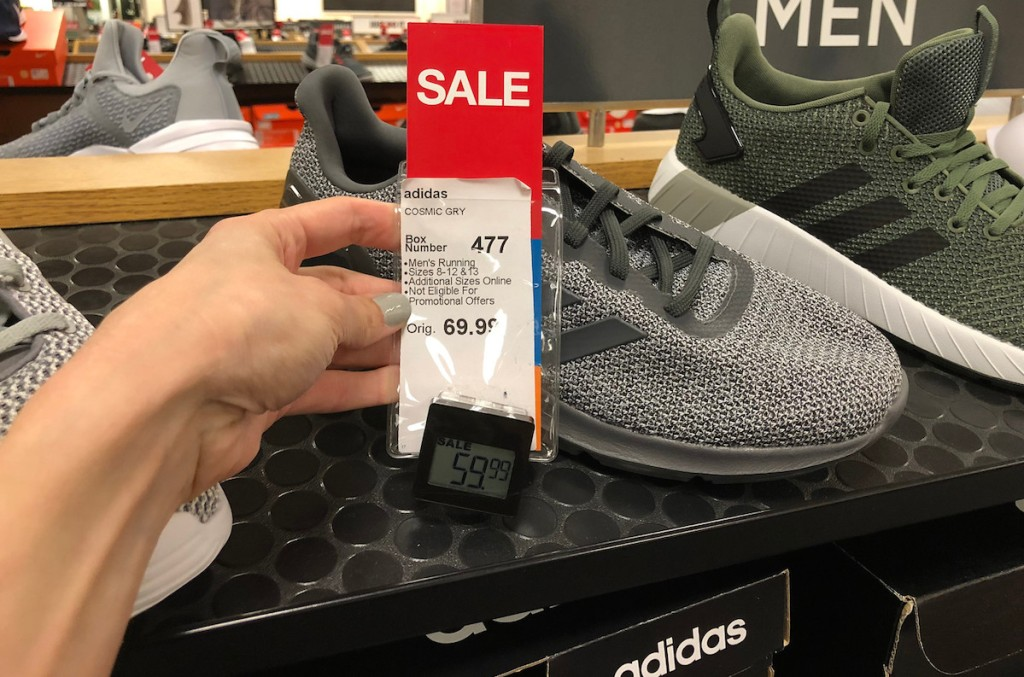 hand holding red sale tag on adidas shoes