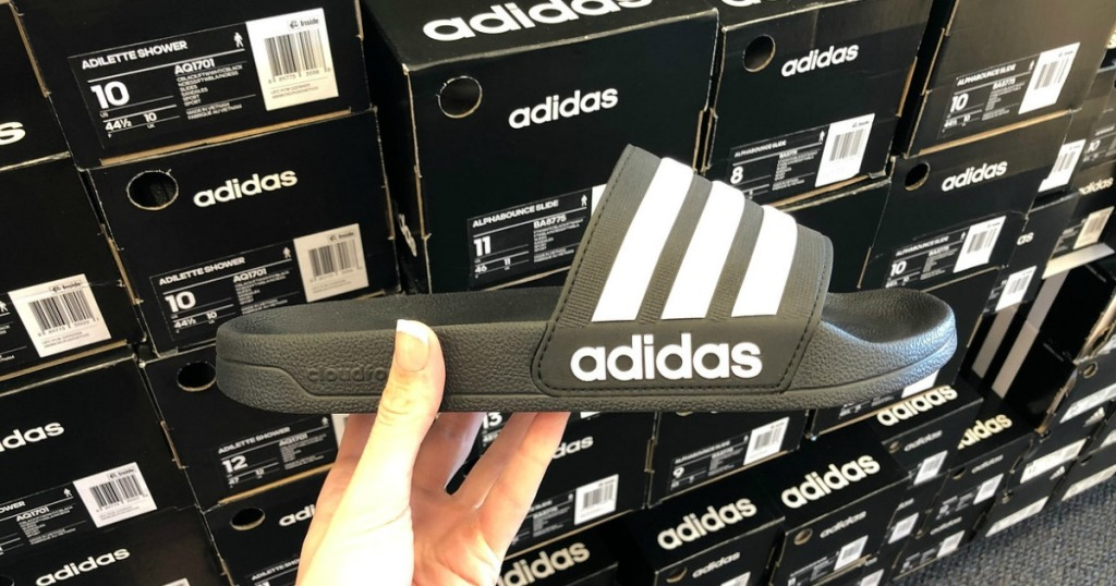 woman holding adidas slides in front of adidas shoe boxes