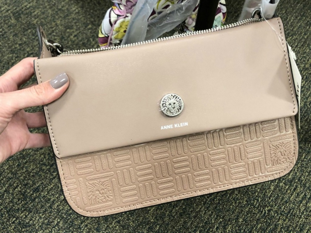 hand holding tan purse