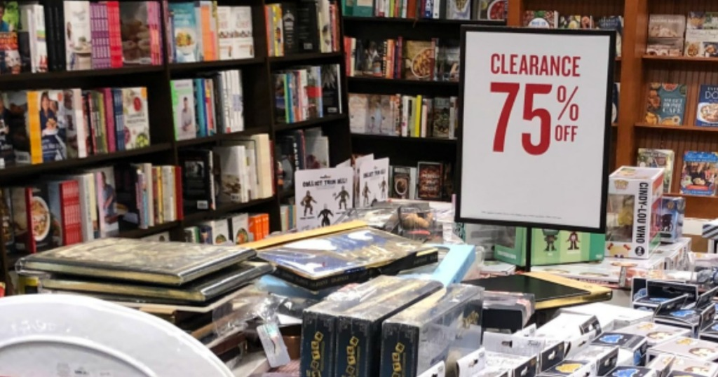 piles of books inside store by clearance sign