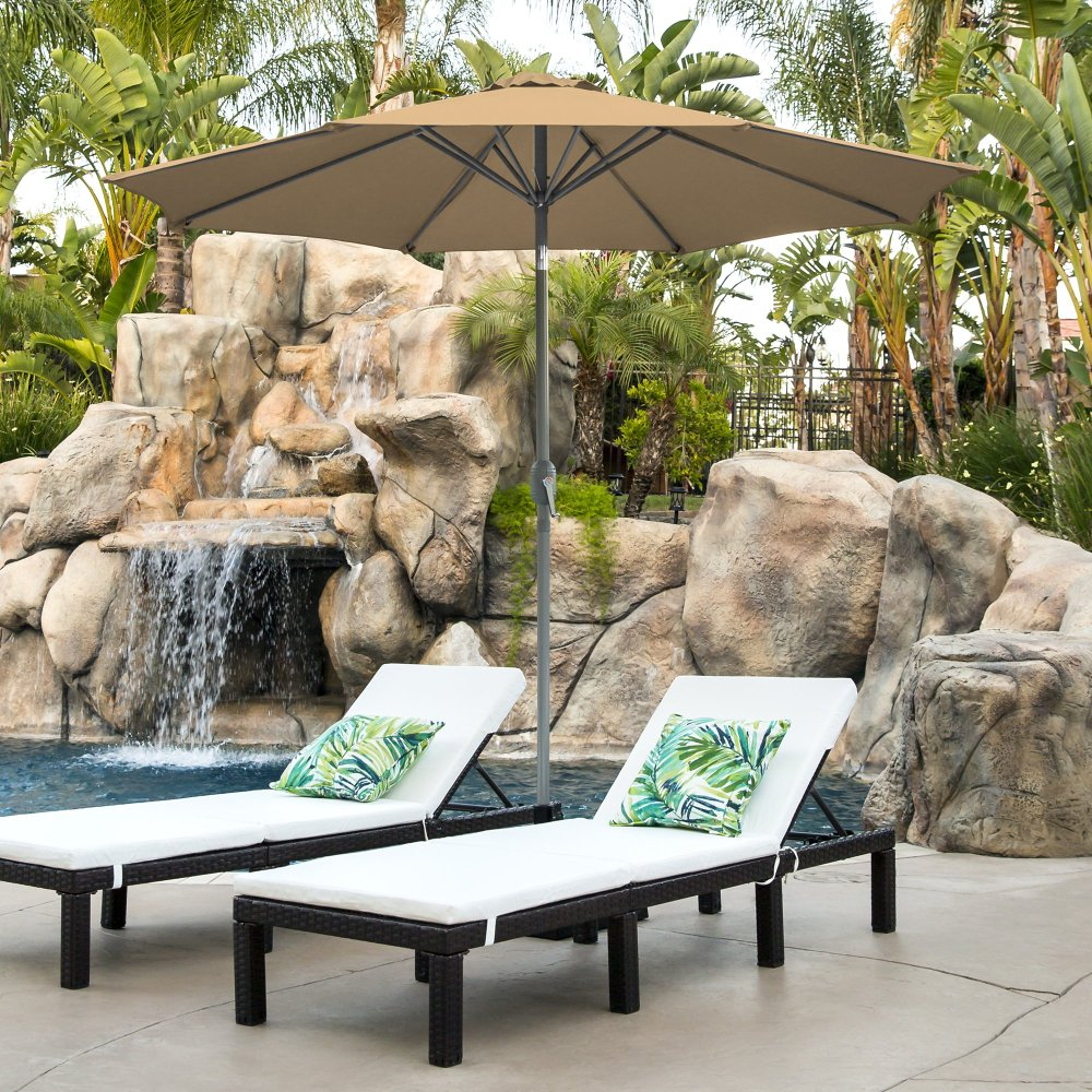 tan patio umbrella outside over two lounge chairs