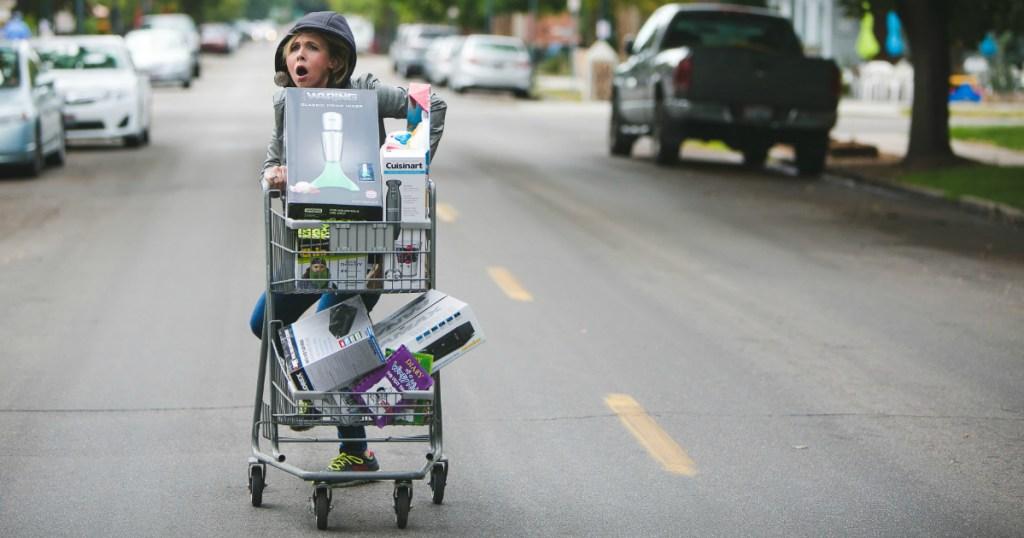 woman pushing shopping cart down street