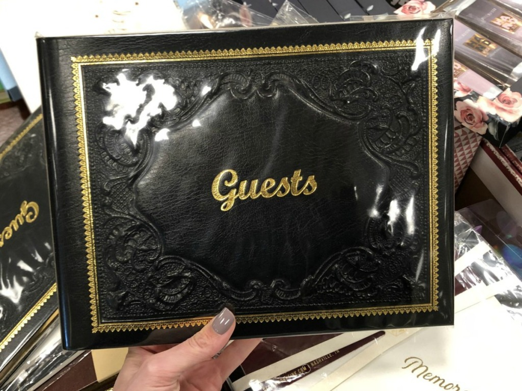 hand holding black book that says guests