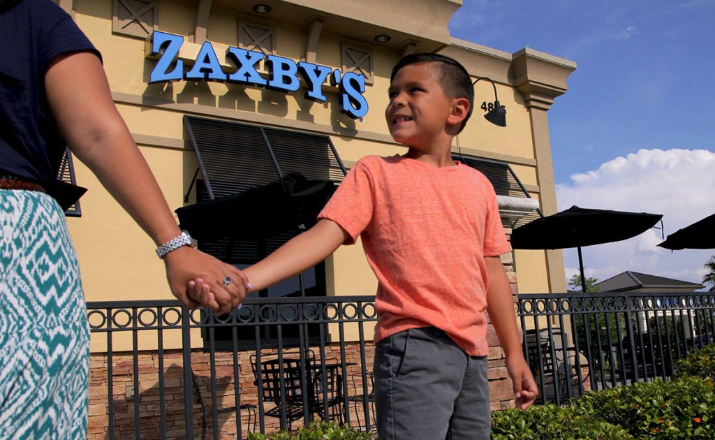 boy and mom holding hands by Zaxby's store front