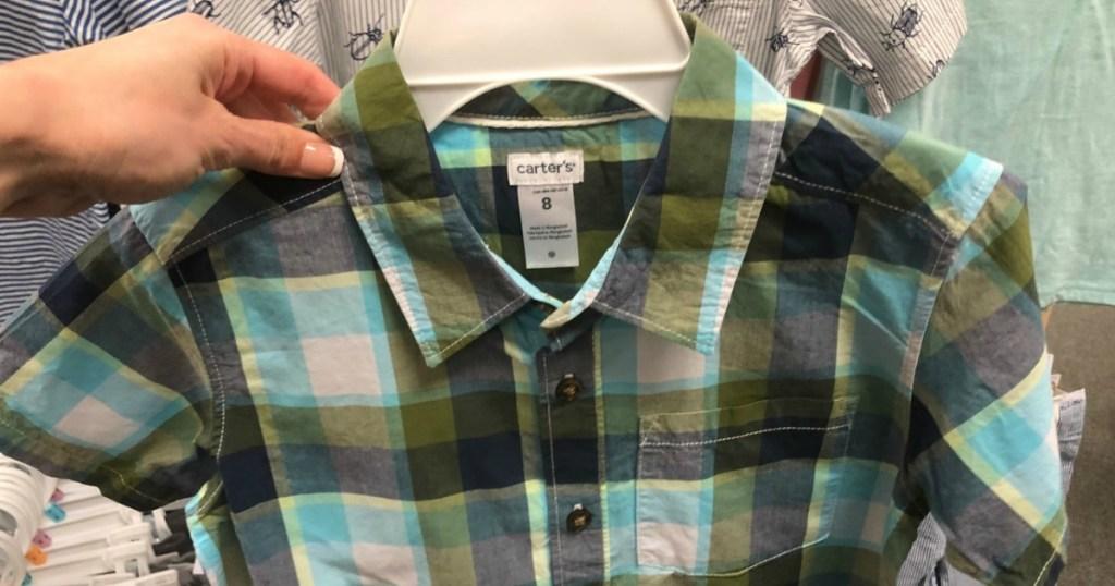 hand holding plaid little boys shirt on hanger