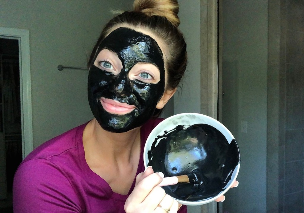 woman wearing black charcoal face mask