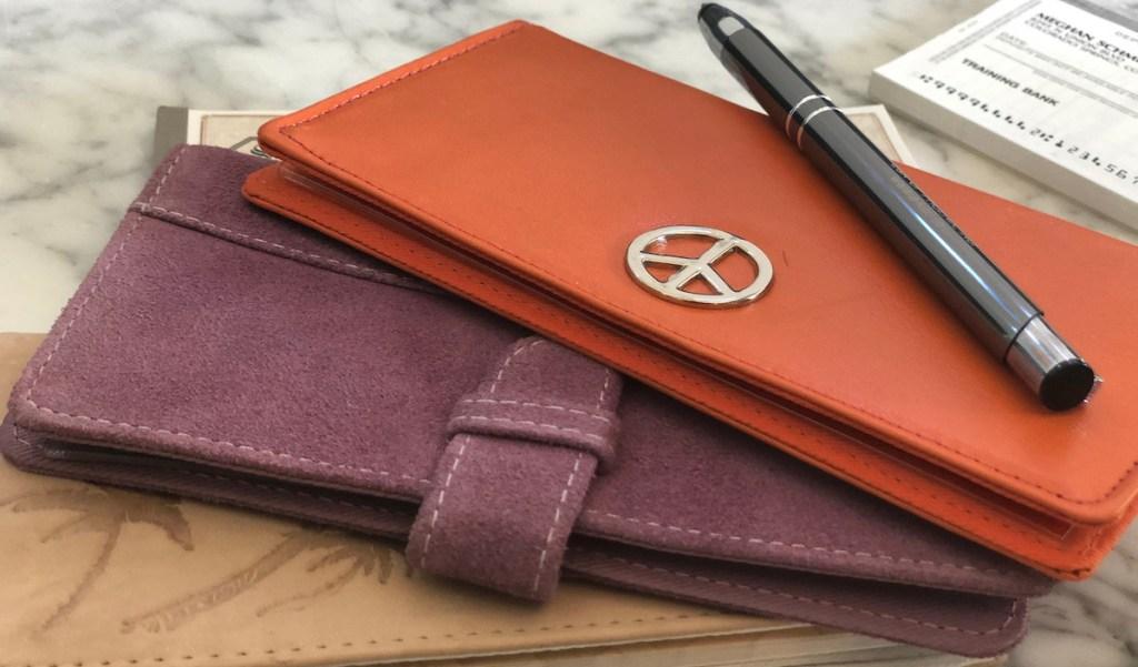 purple and orange checkbooks cover with pen