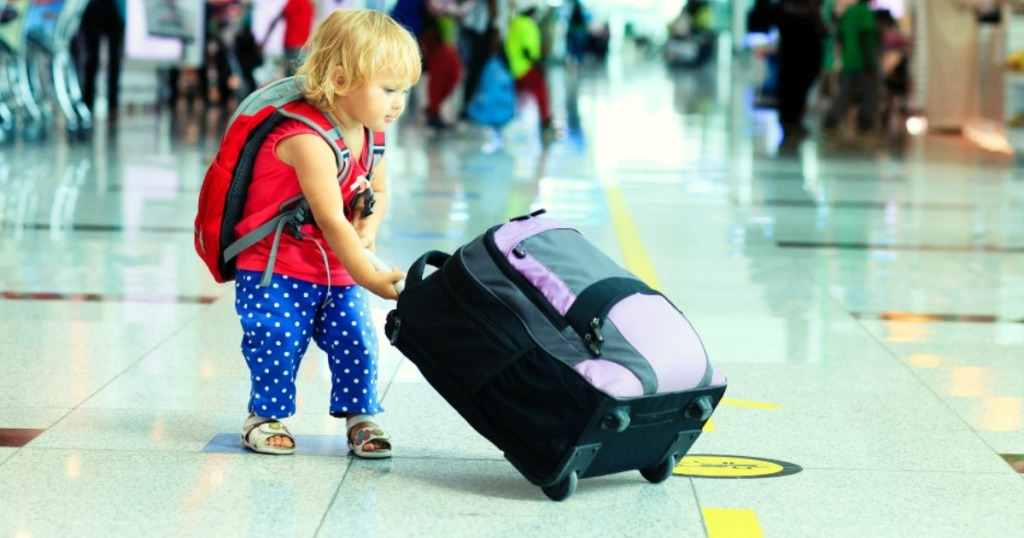 child at the airport with carry on luggage