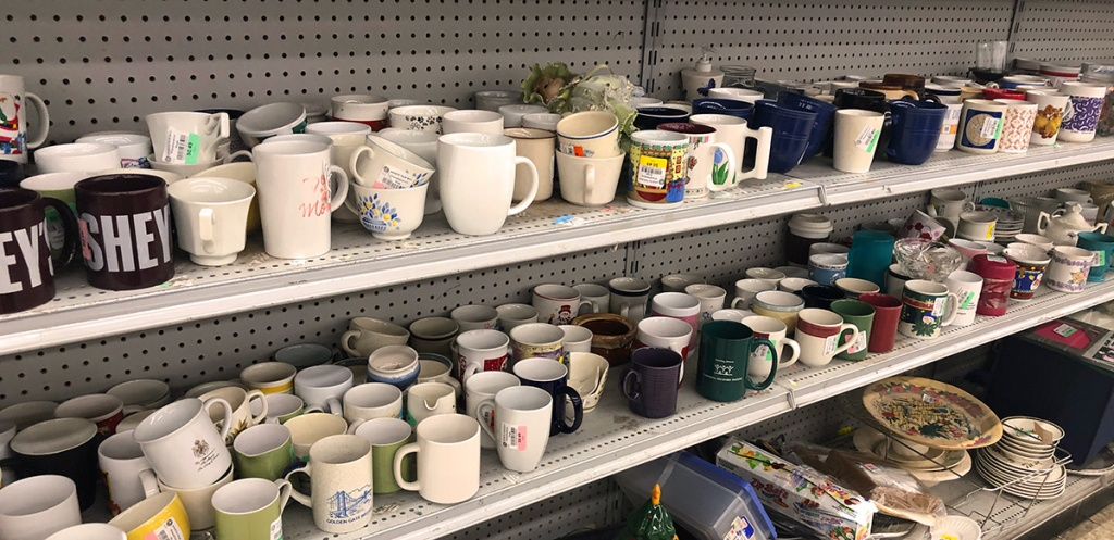 coffee mugs on shelves at thrift store