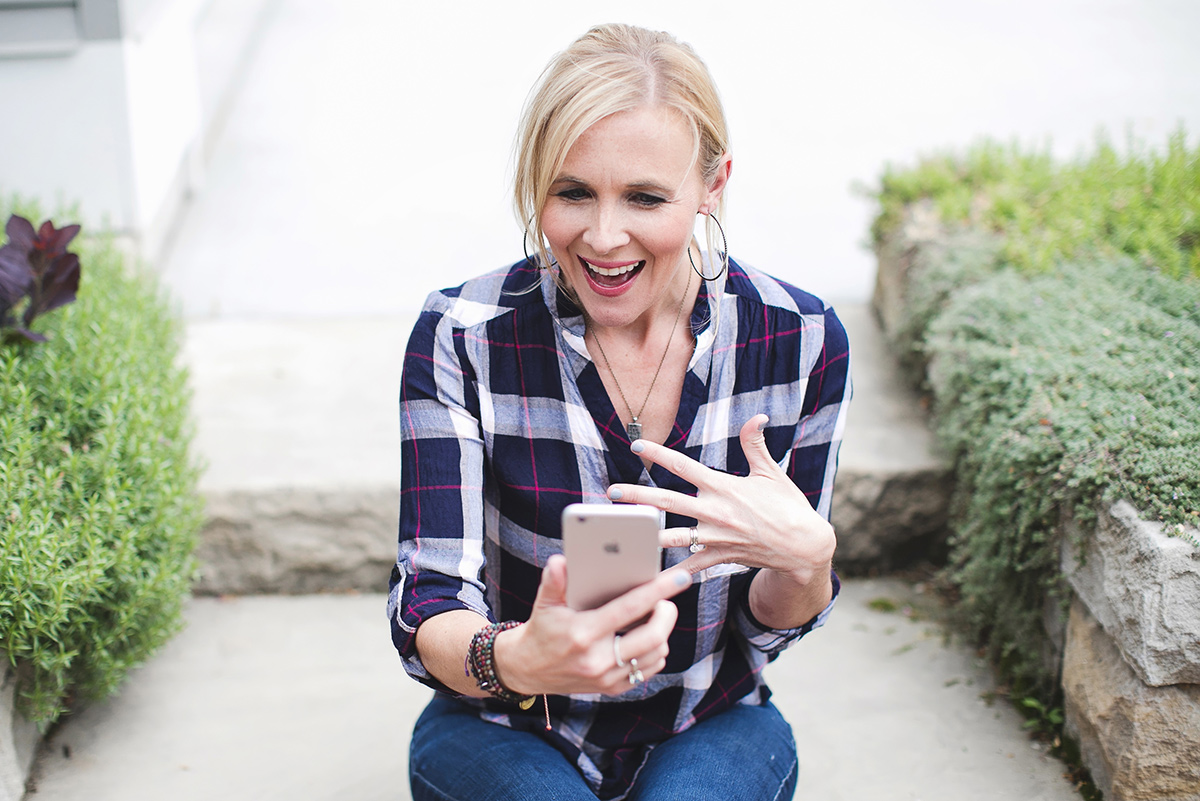 woman looking at iphone excited and happy