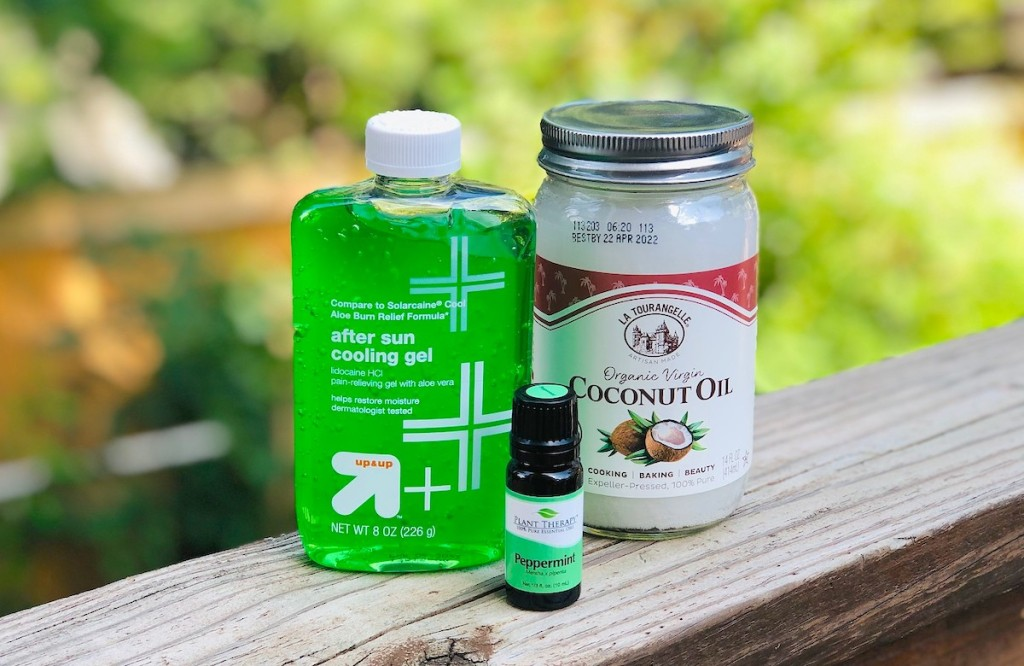 bottle of green aloe vera gel jar of coconut oil and peppermint essential oils on wood railing outside