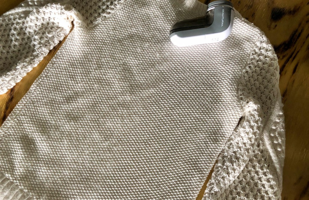 cream sweater laying flat on table with fabric shaver
