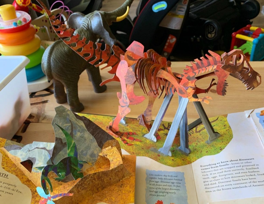pop-up book with dinosaur coming out of it