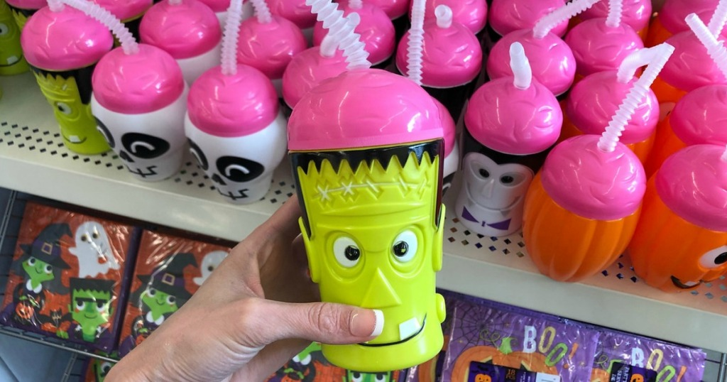 hand holding plastic cup that looks like frankenstein