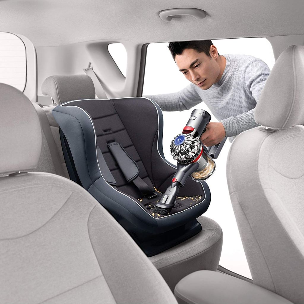 man vacuuming car seat with Dyson V7 handheld vacuum