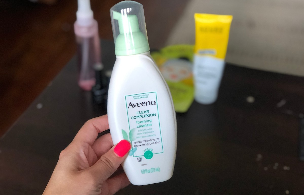 hand holding a bottle of aveeno face wash