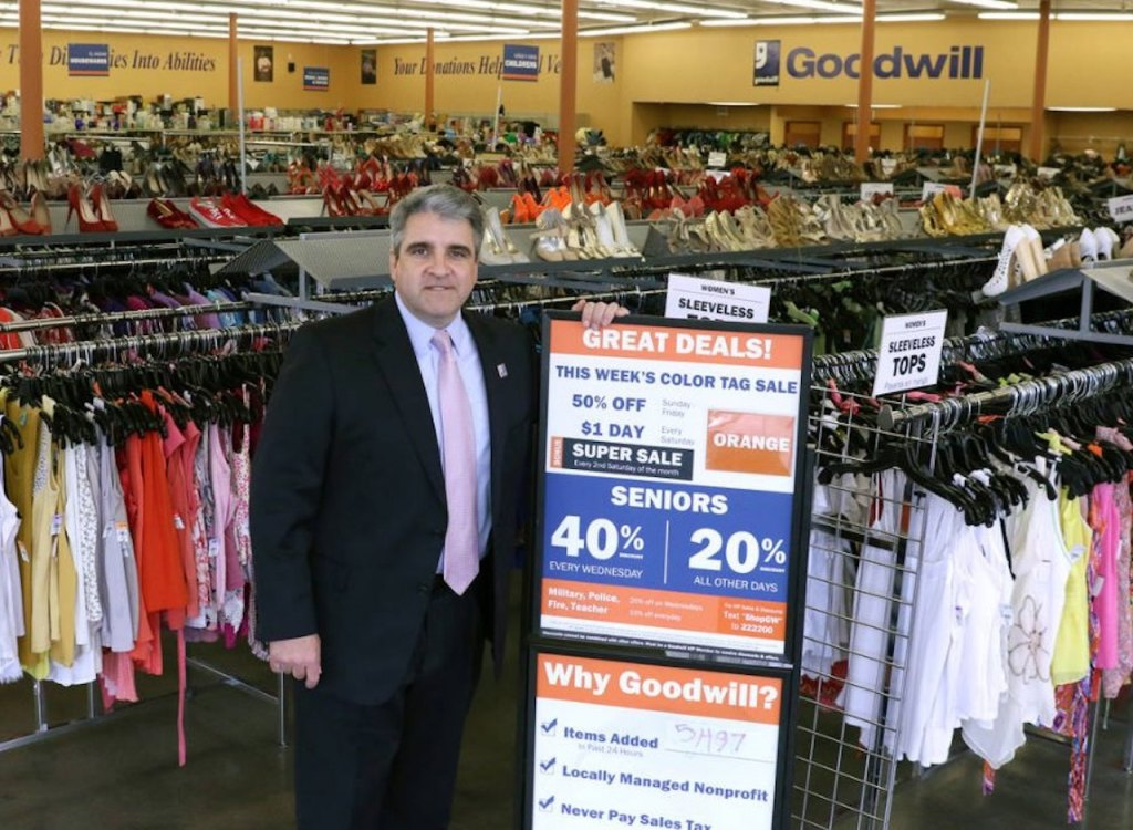 man standing by Goodwill sale sign