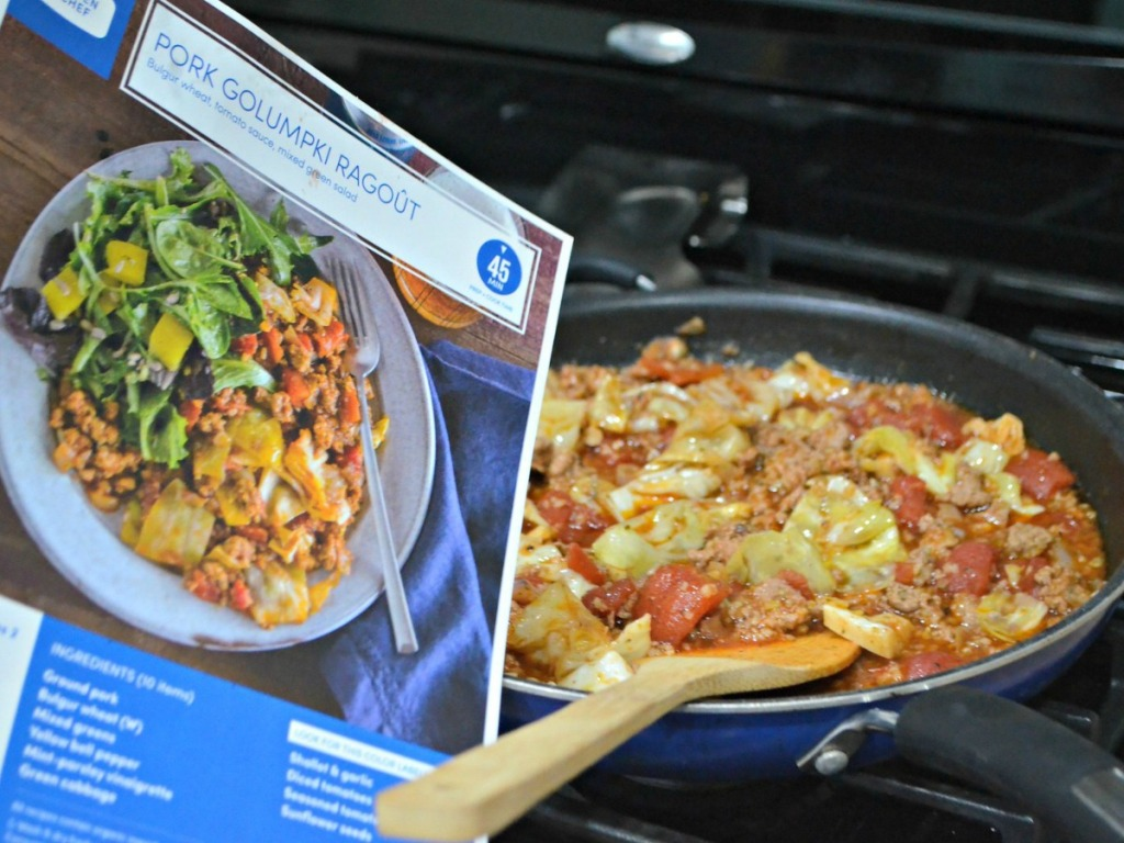 skillet on stove with recipe card next to it