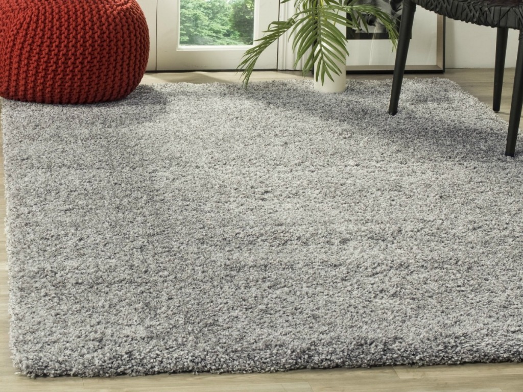 silver rug on wood floor with red chair