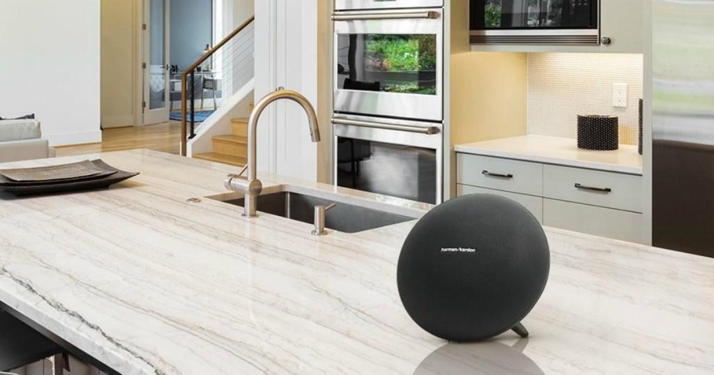Black bluetooth speaker on counter in kitchen