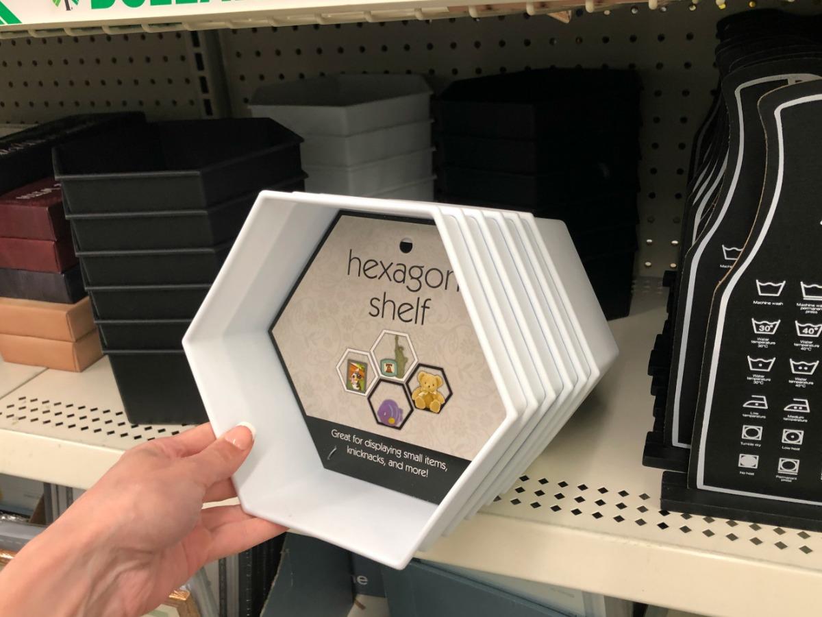 woman holding white hexagon shaped shelf in-store