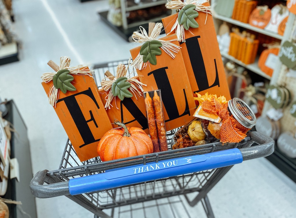 fall sign and various home decor in top of store cart