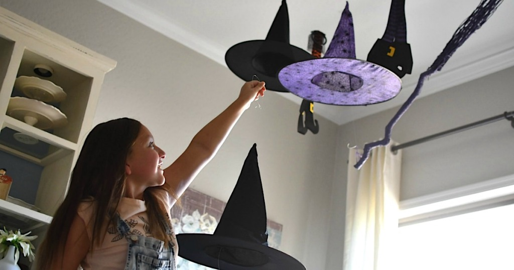 girl putting witch hats on ceiling to hang