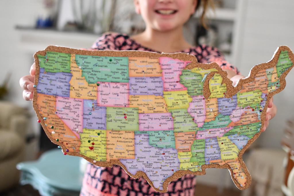 little girl smiling holding DIY travel map