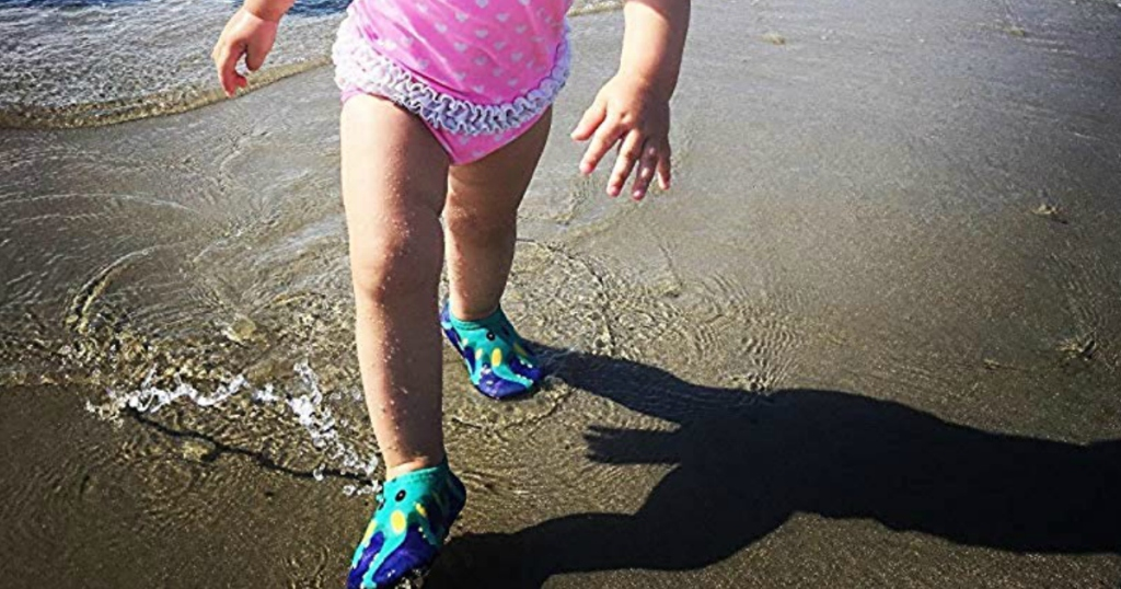 baby walking on beach with water shoes