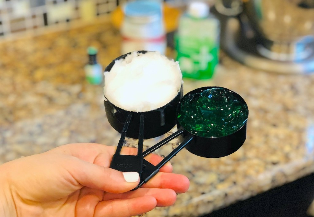 hand holding two black measuring cups with white and green gels
