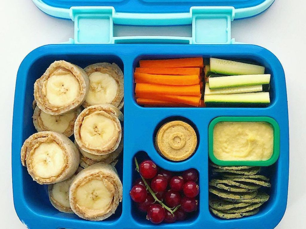 blue kids bentgo box with banana and peanut butter, carrots, grapes, and more
