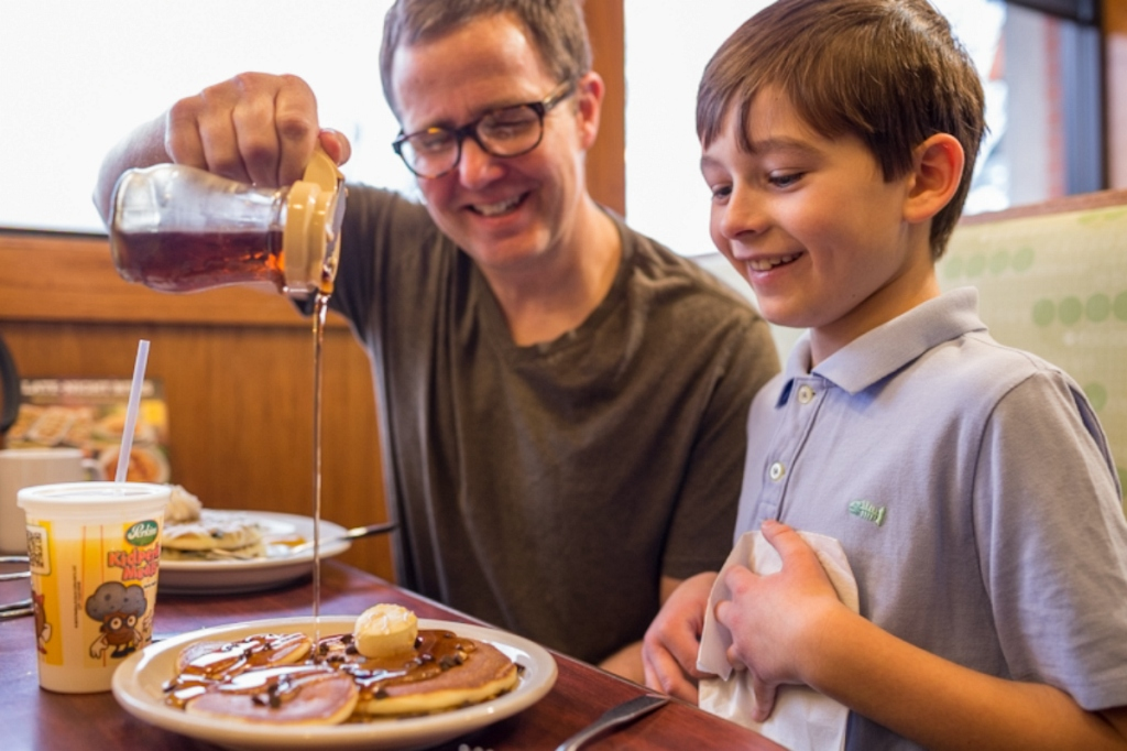 dad pouring syrup on kids pancakes