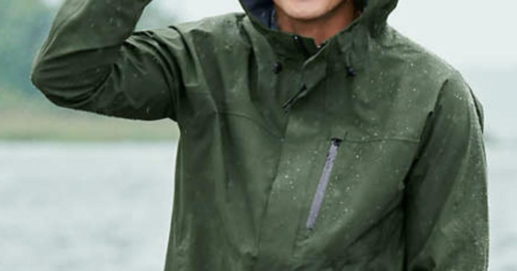 man wearing a green rain jacket outside in the rain