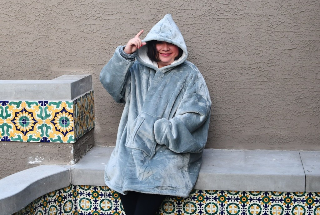 woman wearing an oversized gray blanket hoodie