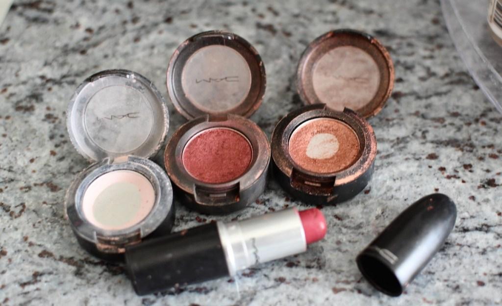 three MAC eyeshadows and pink lipstick on granite counter