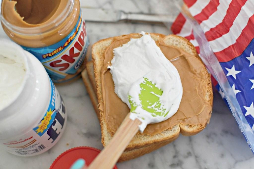 spreading marshmallow fluff on a peanut butter sandwich