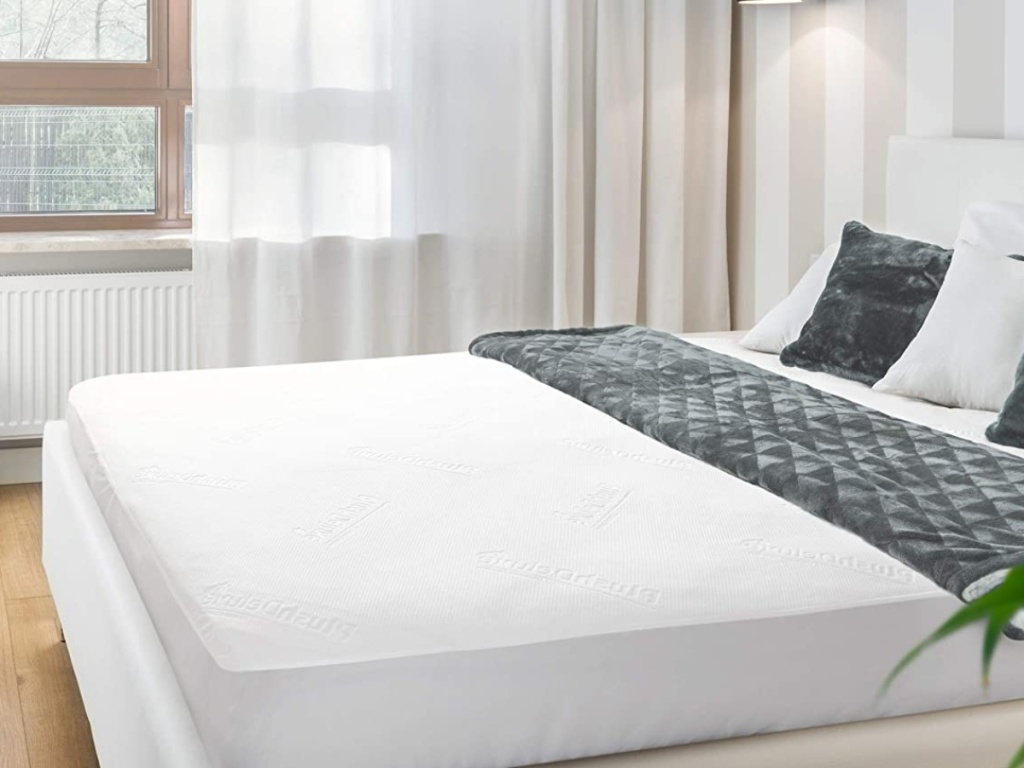 unmade bed with mattress protector