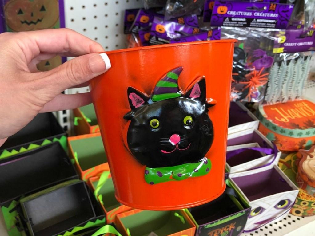 hand holding little orange bucket in store