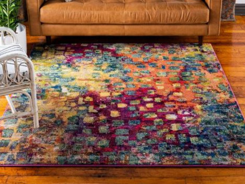colorful rug on wood floor with white chair and orange couch on rug