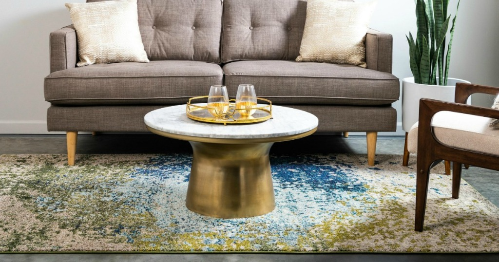 multi-colored rug on gray hardwood floor with table and couch on it